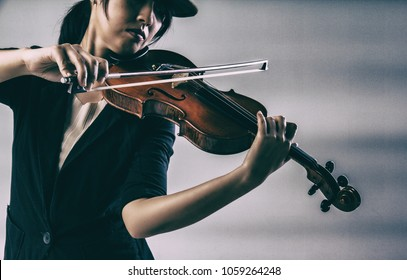 The abstract art design background of the lady is playing violin,in classic old film style,graing flim tone,blurry light around.