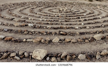 Abstract , artistic , centric round  stone garden for visitors of  the  historic, old town Rhyolite the Nevada desert. Monochromatic because all colors appear soft grey /brown tones. Afternoon sun.