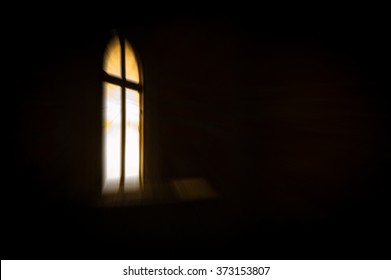 Abstract artistic dark blur glowing window with a cross in the darkness, with copy space for text