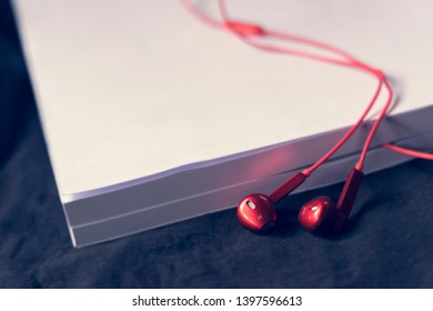 Abstract audio book concept,Red headphones with white books.Learning through sound,Without having to read from texts.Innovation and Education Technology In the 21st century.Selective focus.