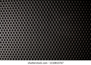 Abstract background is a black metal grid for the speaker close-up. Details audio equipment. Soft focus. Black iron speaker grid texture