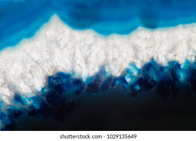 Abstract background, blue agate slice mineral with dark area on the bottom, white crystallized zone in the middle and blue part on the top