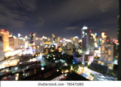 Abstract background from blurred business city center light  from office building downtown at night with urban night light bokeh defocused background.  cityscape at twilight time.