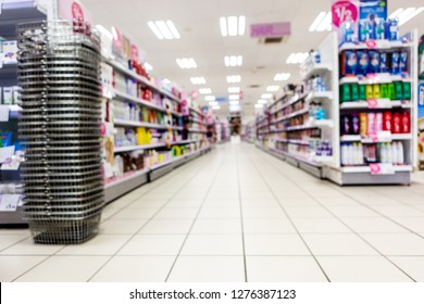 Abstract background blurred photograph of an aisle with shelves in bright modern drugstore at supermarket shopping center.