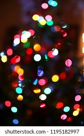 An abstract background of blurred rainbow colored Christmas Tree lights.