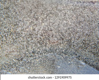 Abstract background, boiling water with small bubbles and blurred lights, quicksilver or liquid silver