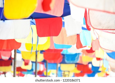 Abstract background of bottom view a part of multicolors umbrella install on beach for welcome many tourist in the world, summer destination in asia, Chonburi, Thailand.