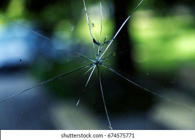 Abstract background of cobweb cracks  The texture of the broken cracks. Close-up of a cracked glass. Dirty scratched broken glass of a office door