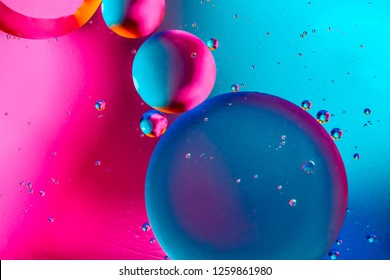 Abstract background with colorful pink blue gradient colors. Oil drops in water abstract psychedelic pattern image.