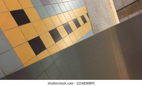 Abstract background created from juxtaposition of stainless steel wall covering, ceramic floor tiles and concrete in LA Metro station