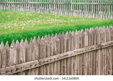 Abstract Background Detail of a wooden picket fence around grass lawn with dandelions.