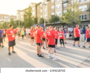 Abstract background employee in uniform attend 5K Corporate Challenge race in Richardson, Texas, USA. Blurred diverse multiethnic group of participant at urban sport event, healthy lifestyle concept