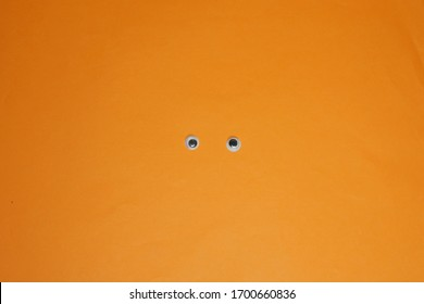 abstract background with eyeballs on orange paper.