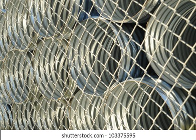 Abstract background of galvanized metal culverts behind chain link fence