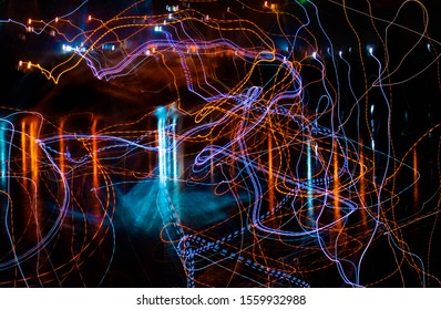 Abstract background with glowing blue, orange and purple lines, fluorescent effects and beautiful light reflection in the water at ngiht. Garopaba, Santa Catarina, Brazil. Neon, technology effect.