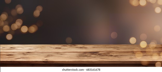 Abstract background with golden bokeh and empty wooden table for a celebratory concept