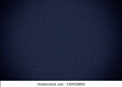 abstract background of grain or noise from digital camera sensor after increasing exposure by software with vignette appearing on the corners, static TV noise, poor signal