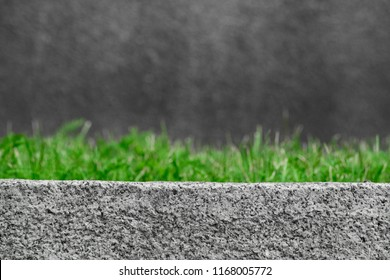 Abstract background with a gray curb stone and green grass