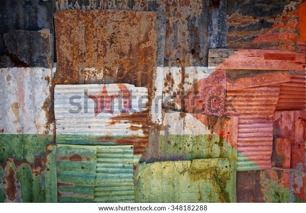 An abstract background image of the flag of Western Sahara painted on to rusty corrugated iron sheets overlapping to form a wall or fence.