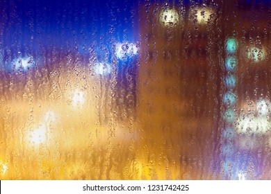 Abstract background with light colorful multi-colored highlights on a wet glass in rainy night weather.
