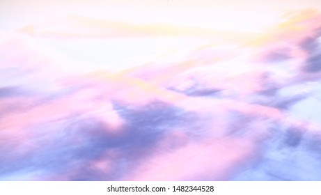 Abstract background in light pink, blue and yellow pastel colours. Image reworked from originally being a sky with clouds and sunset into an abstract futuristic landscape.