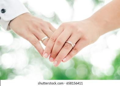 Abstract background of lovers couple holding hands with wedding ring on nature background.