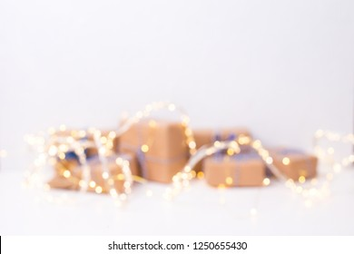 Abstract background. Many  wrapped boxes with presents  and fairy lights on blurred background. Place for text. Winter holiday, Christmas, New Year.