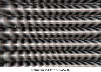 Abstract background of metallic gray long pipes with thread