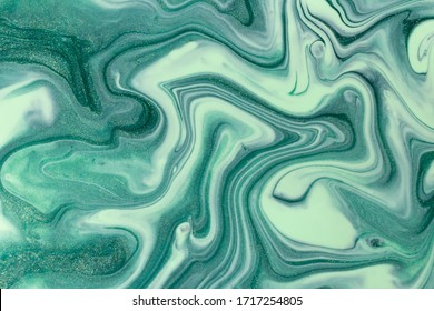 Abstract background of mixed shades of green nail polish with a pastel marble pattern. Liquid colorful background paint creative pastel cold green hue with shimmer
