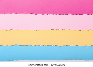 abstract background of multi-colored stripes of torn cardboard lying horizontally, top view,concept stationery business