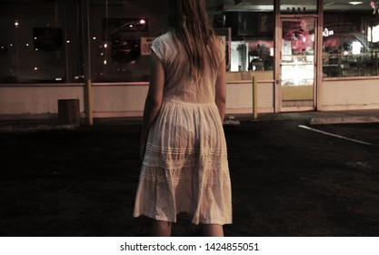 An abstract background of a mysterious  woman clothed in a white dress appears to be sleepwalking to the nearby donut shop.