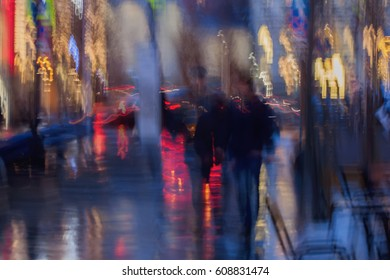 Abstract background in naturale blue tones. People walking down the city street in rainy evening. Intentional motion blur. Concept of seasons, weather, modern city.