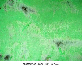 Abstract background of an old worn green wooden surface with black patches