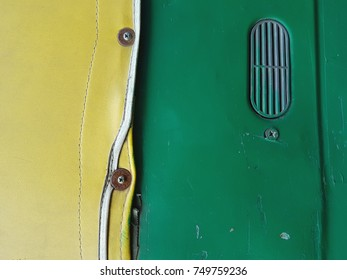 Abstract background, on the left a bright lemon tight fabric with rivets, on the right a green surface with an oval recess.