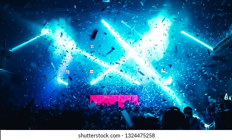 Abstract Background of Party Concert.Cheering happy joyful crowd with raised hands, falling confetti at concert,music festival. Crowd happy and joyful in club.Blur image of concert,Celebration party.