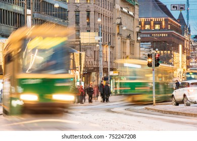 Abstract Background Photo With Tram Departs In Motion Blur From A Stop On Mannerheim Avenue In Helsinki. Night View Of Mannerheim Avenue In Kluuvi District In Evening Or Night Illumination.