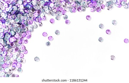 Abstract background with purple sequins on white  background. Decorative accessories for sewing and embroidery. Circle shape shining paillettes. Template for card. Flat lay, top view, copy space