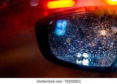 Abstract background with rain drops on the car side view mirror. Blur lights. City taxi.