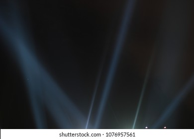 Abstract background. Searchlights shining beams of light into the black sky.