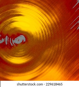 Abstract background of spin circle radial motion blur in yellow gold, red, and grey, with sand texture
