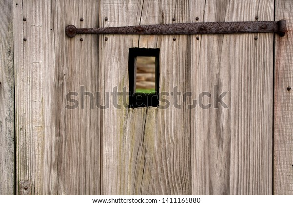 Abstract Background Texture Detail of an old wooden door with an Iron Hinge and a hole in the middle.