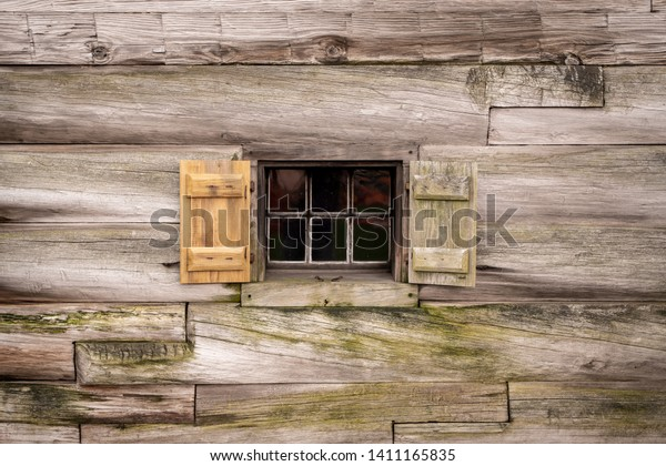 Abstract Background Texture Detail of a window with open shutters on a wood cabin wall.
