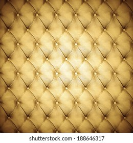 Abstract background texture of an old natural luxury, modern style leather with rhombs. Classic gold, black and dark brown grungy skin of retro wall, door, sofa or studio interior with metal buttons.