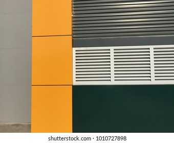Abstract background texture or wallpaper of zooming closeup colorful wall of a modern decorative factory consists of yellow, dark green , grey and white window frames
