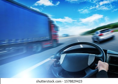 Abstract background with a truck with a trailer, truck steering wheel and a silver family car in motion against sky with blue lights