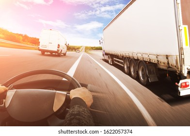 Abstract background with a truck with a trailer, truck steering wheel and a big white van against sky with orange lights
