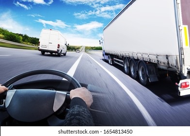 Abstract background with a truck with a trailer, truck steering wheel and a big white van against sky