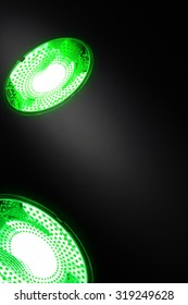 Abstract background with two compact electric lamps in green color and beam of light accenting a place for a logo or text in the center of composition. Hint of Green technologies or energy saving.