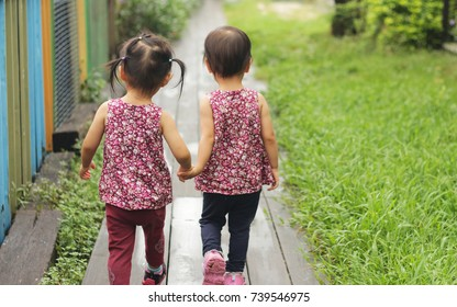 abstract background. two twins girls hand in hand walking on the meadow in park. From back and rear