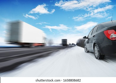 Abstract background with two white box trucks in motion and a black family car on the countryside winter road in motion with snow against a blue sky with clouds